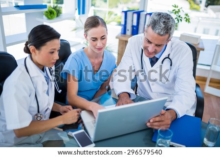Doctors and nurse looking at laptop in medical office - stock photo