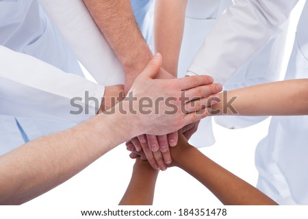 Doctors and nurses stacking hands. Isolated on white - stock photo