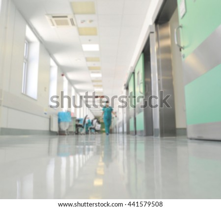 Doctors and nurses walking in hospital hallway, blurred motion.