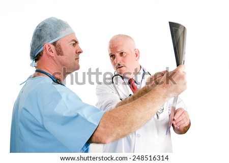 Doctors discussing x-ray results.  Focus on the older doctor pointing out a problem to his younger intern.  Isolated on white.   - stock photo