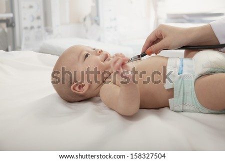 Doctors hand checking the heartbeat of baby - stock photo