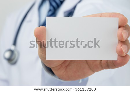 Doctors hand holding a business card - stock photo