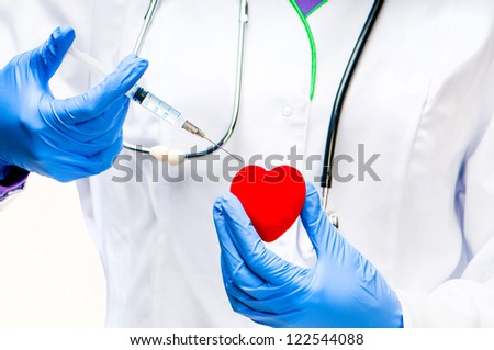 Doctors hands with Syringe and red heart - stock photo
