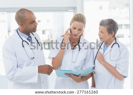 Doctors having an important phone call in medical office - stock photo