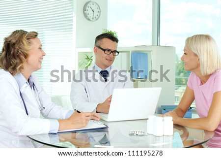 Doctors interacting with patient at medical consultation - stock photo