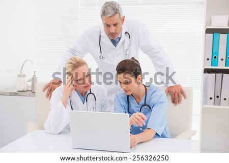 Doctors looking at laptop in medical office - stock photo