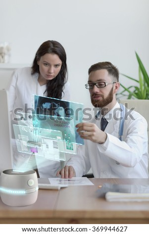 Doctors looking x-ray of his patient at his office. Using futuristic virtual computer interface
