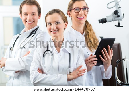 Doctors - male and female - discussing test reports that show on their tablet Computer