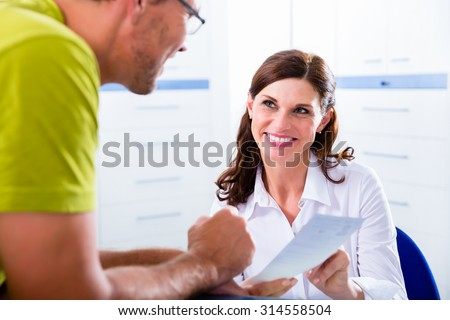 Doctors nurse with telephone in front desk making appointment with patient - stock photo
