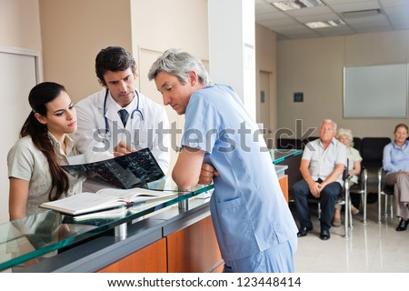 Doctors reviewing x-ray at hospital reception while people sitting in background - stock photo