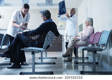 Doctors reviewing x-ray at hospital reception while people sitting in background. - stock photo