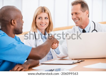 Doctors shaking hands. Two cheerful doctors shaking hands while sitting together with female doctor