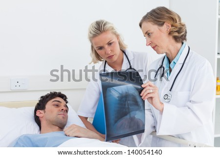 Doctors showing and explaining radiography to a patient - stock photo