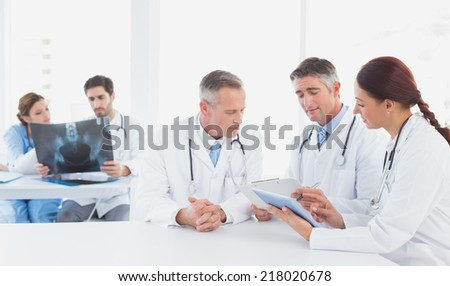 Doctors sitting together with x-rays and other doctors using a tablet - stock photo