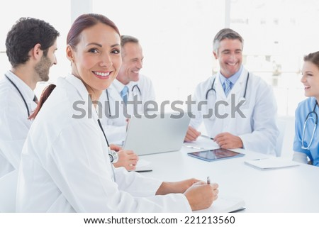 Doctors smiling and working together at work - stock photo