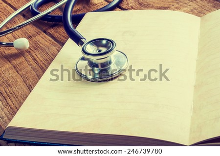 Doctors Stethoscope on a blank notepad with wooden plate for medical concept  in vintage style. - stock photo