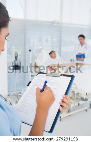 Doctors taking care of patient in hospital room - stock photo