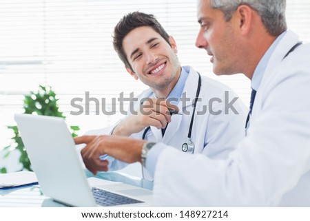 Doctors talking together about something on their laptop in medical office