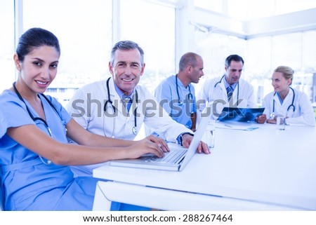 Doctors using computer whiles theirs colleagues looking at Xray in medical office - stock photo