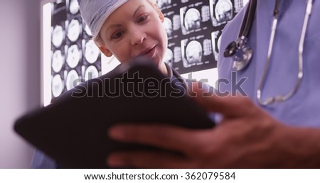Doctors using devices in the office - stock photo