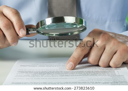 Document. Businesswoman looking through a magnifying glass to contract - stock photo