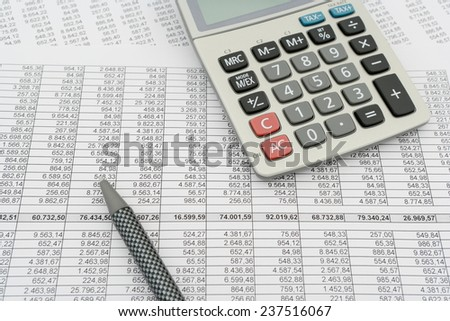 document with numbers in several columns, calculator and pen