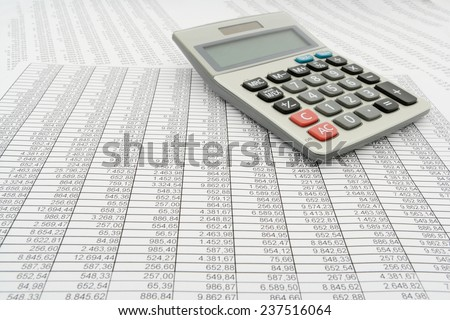 document with numbers in several columns, calculator, low angle view - stock photo