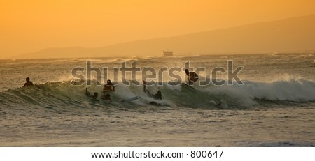 Documentary: Beach life: Surfing at sunset in Waikiki on a calm day - stock photo