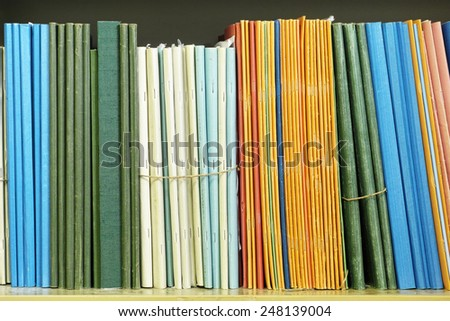 documents aligned on the shelf of a bookcase - stock photo
