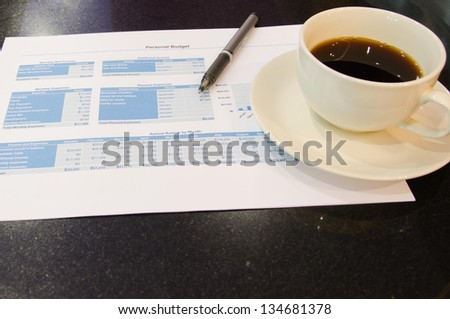 Documents and cup coffee pen placed on the table.