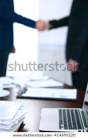 Documents and laptop on the table. Business people shaking hands on the background