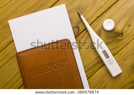 Documents for travel and medicines on a wooden background