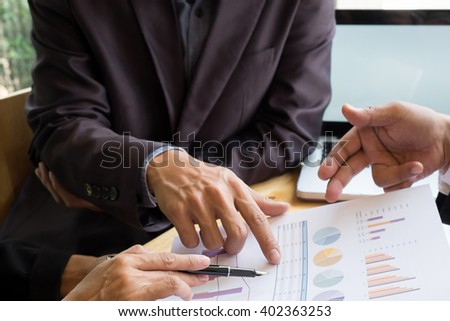 Documents on office table and two men talking.