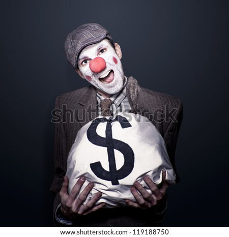 Dodgy Bank Robber Clown Holding Dollar Sign Money Bag While Laughing Out Loud In A Depiction Of Funny Money - stock photo