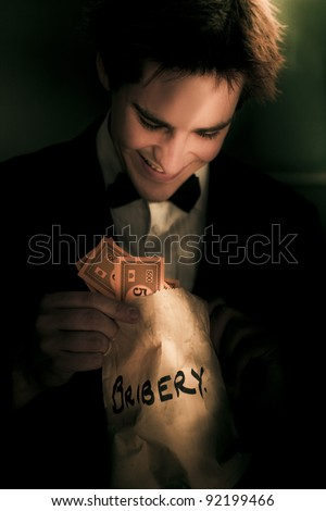 Dodgy Business Deal With A Fraudulent Politician Or Figure Of Authority Looking Into A Bag Of Money In A Representation Of Illicit Deceit And Immoral Behavior - stock photo