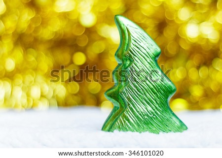 DOF ceramic christmas tree and blurred golden ribbon with bokeh background - stock photo