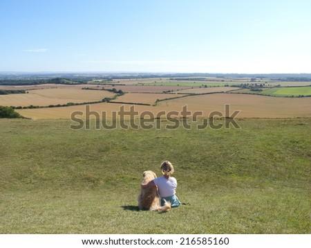 Dog and woman enjoying rolling landscape, White Sheet Down, Wiltshire, United Kingdom - stock photo