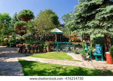 Dog baby garden house with flowers on breeding dog station. Summer garden design with flowers in bloom. Morning blue sky. Red New Guinea impatiens flowers in pots on birch chunk