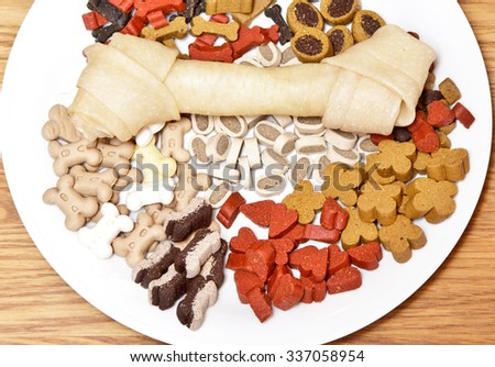 Dog bone and dog candy on a plate - stock photo