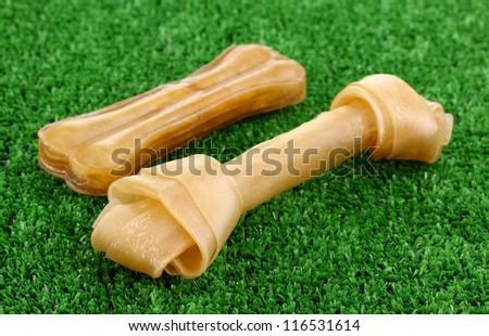 Dog bones on green grass - stock photo