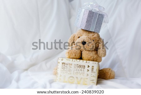 Dog doll with gold and silver gift boxes on white cloth background