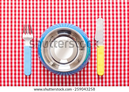 dog food bowl with knife and fork on tablecloth, empty and blank - stock photo
