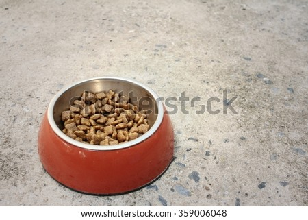 Dog food in bowl on cement background. - stock photo