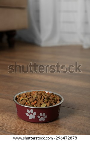 Dog food in bowl on floor at home - stock photo