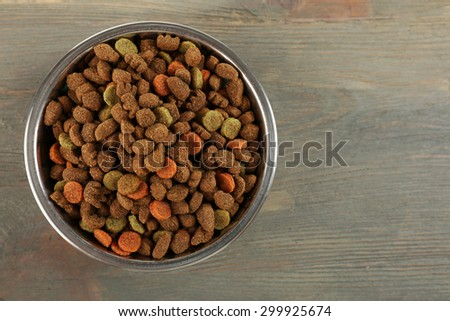 Dog food in bowl on wooden table - stock photo