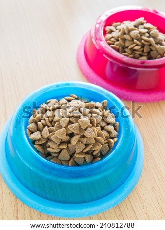 Dog food in color bowl, Shallow of depth in field - stock photo