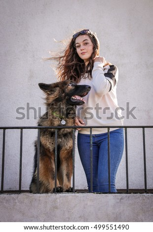 Dog looking at girl who is looking at the camera