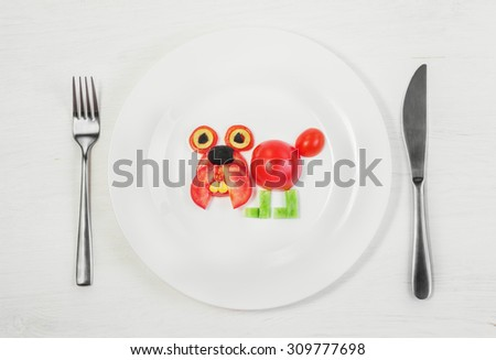 Dog of fresh tomatoes, cucumbers, corn and olives on a plate, fork and knife on the table. Concept of children's breakfast, healthy diet, raw food, vegetarian, vegan, Funny animals from vegetables.  - stock photo