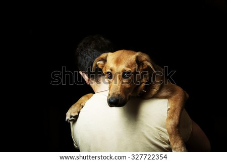 Dog on a man shoulders. Boy holding on his shoulder his puppy on black background.