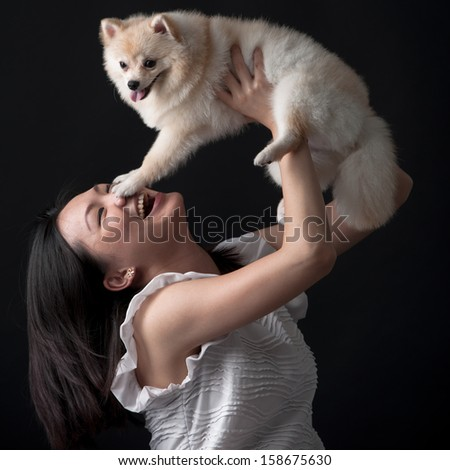 Dog owner holding her dog in the air - stock photo